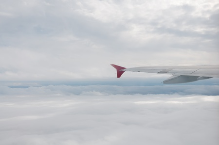 airfoil: Winf of airplane above fluffy white cloudscape