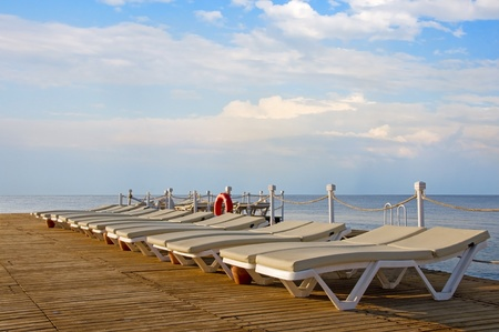 Ten chaise-longues on a wooden pier and sunrise with clouds on the sky Stock Photo - 11787049