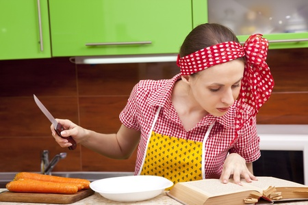 Serious woman in the kitchen with knofe is reading recipe book photo