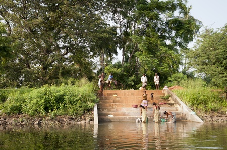 Habarane, Sri Lanka - December 04, 2011: Sri Lankian women are washing clothes in a lake on the stony steps.