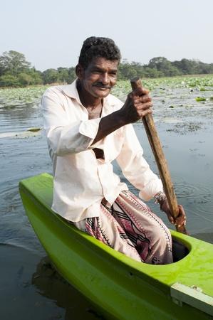 green boat: Habarane, Sri Lanka - December 04, 2011: Smiling Sri Lankian man are floating by small traditional green boat upon a lake.