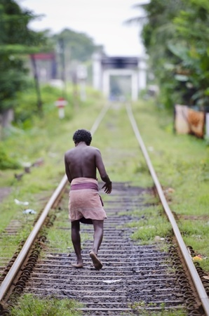 featureless: Bendota, Sri Lanka - December 14, 2011: Lonely unidentified asian man in traditional dress sarong on railway lines. Editorial