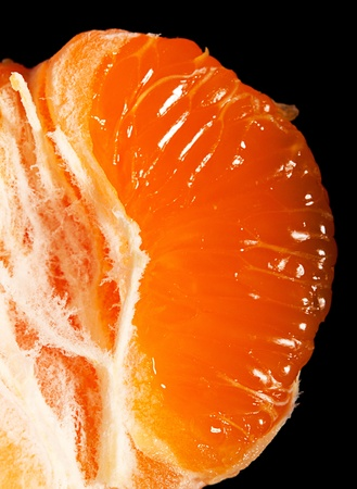 Juicy ripe mandarin segment on black background photo