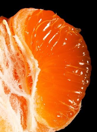 segment: Juicy ripe mandarin segment on black background Stock Photo