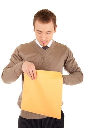 Young business man opens a yellow post package with interest. Isolated on white. photo