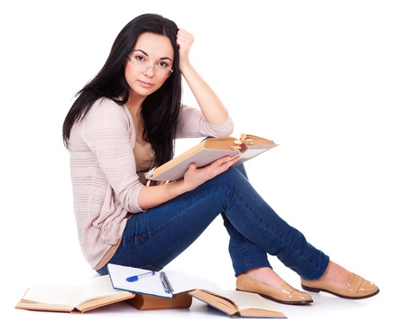 Charming young woman with books sitting on white background
