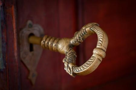 Antique beautiful bronze key in a door