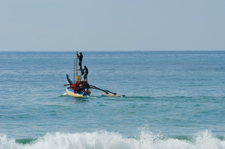 Mirissa, Sri Lanka - December 12, 2011: Traditional Asian small motorboat with four fishermen and fishing net.