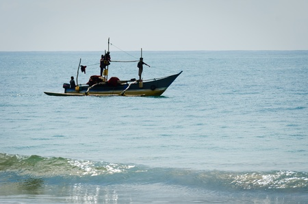 Mirissa, Sri Lanka - December 12, 2011: Traditional Asian small motorboat with four fishermen and fishing net