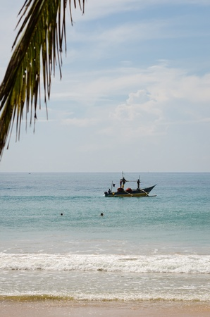 Mirissa, Sri Lanka - December 12, 2011: Traditional Asian small motorboat with four fishermen and fishing net with a palm leaf and beach on front.