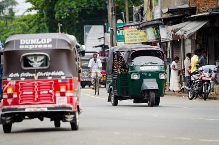 Bendota, Sri Lanka - December 14, 2011: Tuk-tuk is the most popular transport on Asian street. Focus on the green tuk-tuk.
