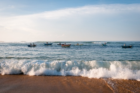 Morning fishing on traditional small wooden boats, Sri Lanka. Focus on the wave on front. Stock Photo - 12522239