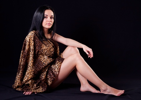 Seductive beauty woman in fur cloth on black background photo