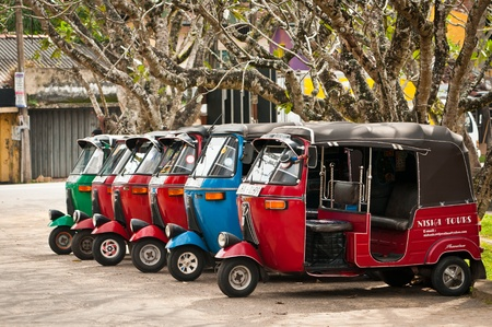 Bendotta, Sri Lanka - December 4, 2011: Row of red, blue, and green tuk-tuks waits for passengers. Tuk-tuk is a popular asian transport as taxi.