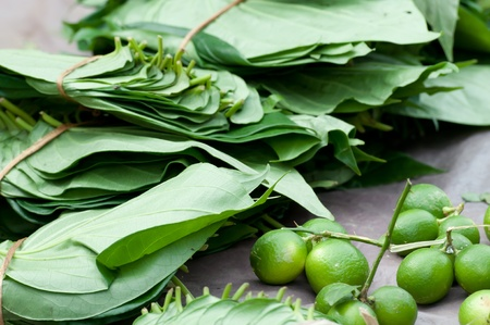 Betel on open market - bunch if leaves and lime. Tradition asian natural chewing gum with narcotic effect photo