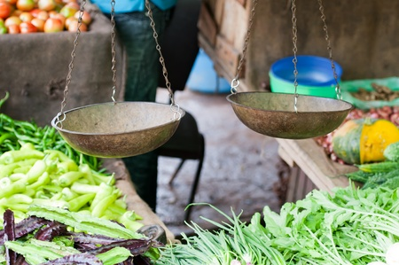 Old scales on open market with vegetables on shelves. Selective focus on the scales. Stock Photo - 12828841