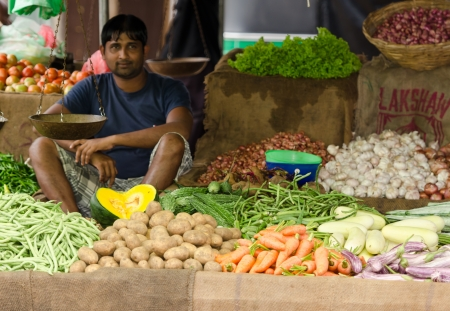 Bentota, Sri Lanka - December 14, 2011:  Asian man sell fresh vegetable and fruits on traditional asian open market