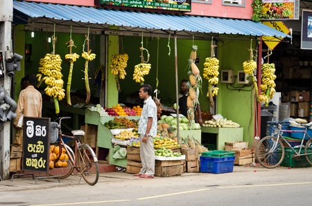 Bentota, Sri Lanka - December 14, 2011:  Asian men in the fresh vegetable and fruits traditional asian shop
