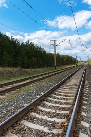 Railway with electric cables and blue sky. Focus on the front rail. Stock Photo - 13915411