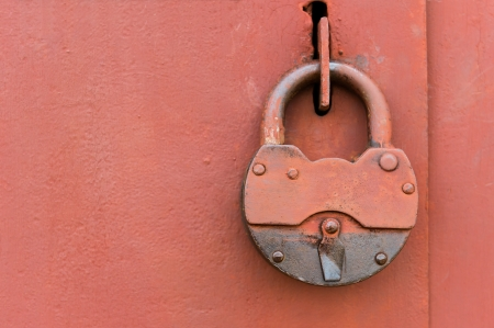 Old big lock on red metal door photo