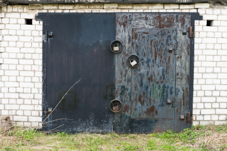 Aged closed black metal garage gate with three big locks on white brick wall photo