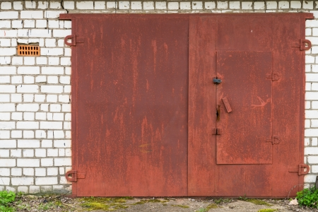Aged closed red metal garage gate Stock Photo - 13957711
