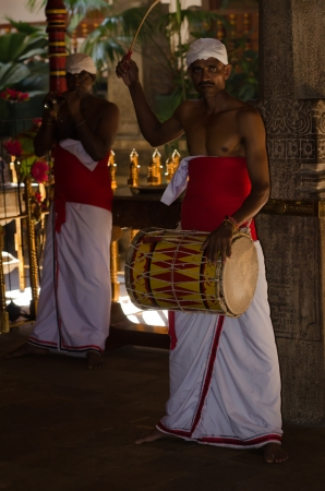 Kandy, Sri Lanka, December 8, 2011- Traditional ceremonial drummer beats the drum in the Temple of the Sacred Tooth Relic Flame