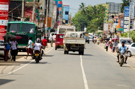 Matara, Sri Lanka - December 10, 2011: Intensive traffic on a narrow asian street with pedestrians, motobikes and cars.