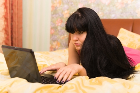 Concentrated young woman with a laptop in bed