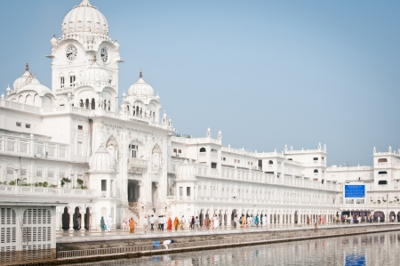 Amritsar, India - August 26, 2011: Pilgrims walk in the Harmandir Sahib Complex, the spiritual and cultural center of the Sikh religion Stock Photo - 14612655