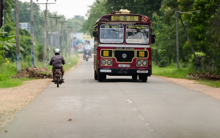 Habarana, Sri Lanka - December 6, 2011: Regular public bus from Colombo to Sri Pura and motorbikes. Buses are the most popular public transport type in Sri Lanka. Stock Photo - 14612656