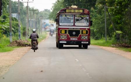 Habarana, Sri Lanka - December 6, 2011: Regular public bus from Colombo to Sri Pura and motorbikes. Buses are the most popular public transport type in Sri Lanka.