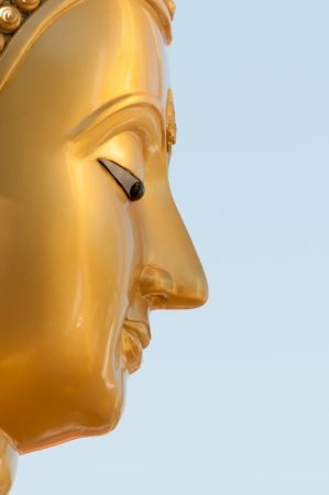 Buddha face in profile with blue clean sky on background photo