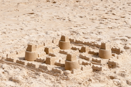 Kids sand castle construction on clean sandy beach photo