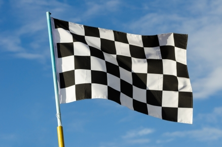 Checkered flag with blue sky on background photo