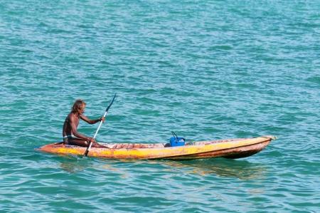 bronzed: Phuket, Thailand - January 19, 2012: Bronzed Thai fisherman on small boat rows across blue sea