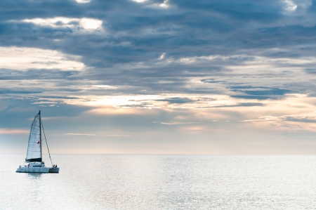 Sailing yacht in sunset on tranquil sea and cloudy sky