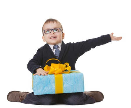 Small sitting boy in spectacles with big present on white background Stock Photo - 14697092