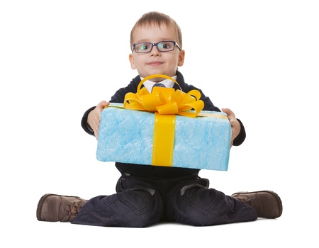 Small sitting boy in spectacles holds a big blue present on white background Stock Photo - 14697090
