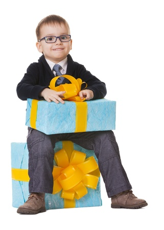 Small happy boy in spectacles with big presents on white background Stock Photo - 14697095