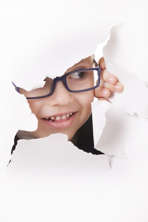 Curious kid in spectacles looks through a hole in white paper photo