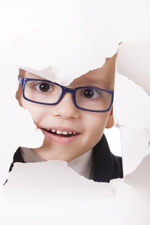 Curious kid in spectacles looks through a hole in white paper Stock Photo - 14697096
