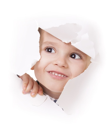 Curious kid looks up through a hole in white paper