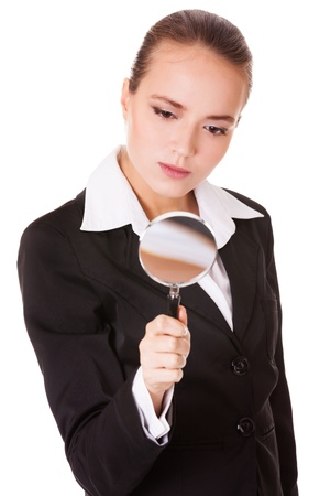 spy glass: Attentive young business woman looking into a magnifying glass isolated on white background