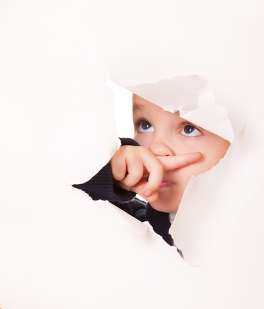 Guilty kid looks up through a hole in white paper photo