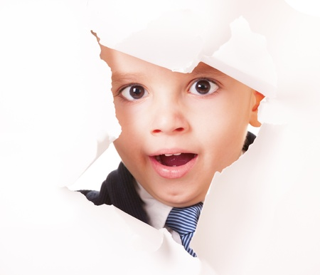 Yawning kid looks up through a hole in white paper photo