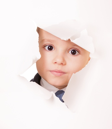 Serious kid looks through a hole in white paper Stock Photo - 14798432