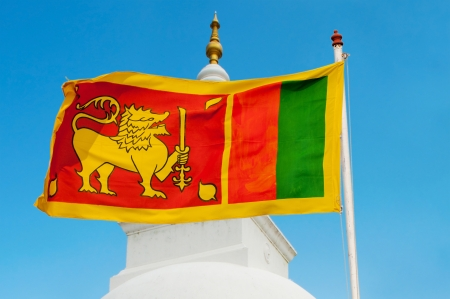 Sri Lanka flag on flagstaff with blue sky and traditional stupa on background  Stock Photo - 14934003