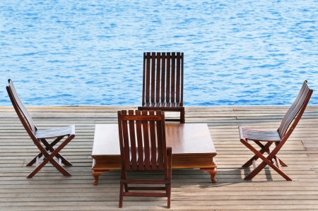 Wooden area with chairs and table on calm blue water photo