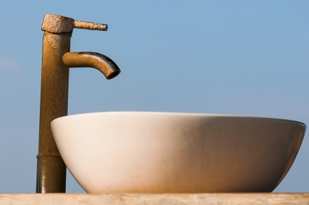 Washbasin and tap covered by limescale with blue sky on background  Focus on the tap   photo